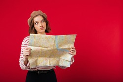Portrait of a confused woman holding city guide map isolated over pink background