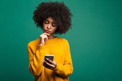 Portrait of a confused young african woman wearing sweater standing isolated over green background, using mobile phone