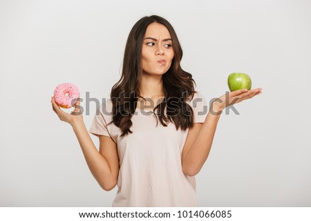Portrait of a confused young asian woman choosing between donut and green apple isolated over white background