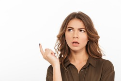Portrait of a confused young woman looking away at copy space isolated over white background