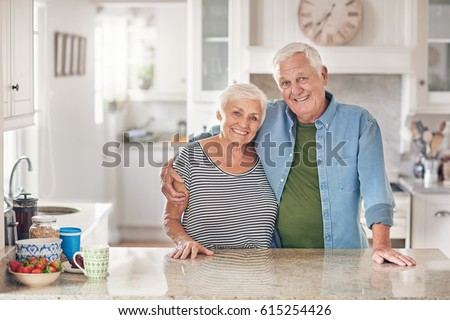 Portrait of a content senior man with his arm around his wife's shoulder standing together in their  kitchen at home