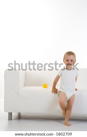 Portrait of a content young child in one piece white clothing, standing leaning against a white couch/sofa in a room with white floor and walls.