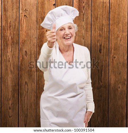 portrait of a cook senior woman doing a good gesture against a wooden wall