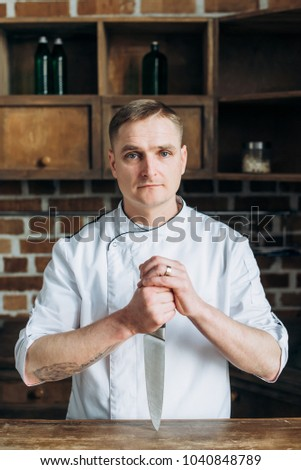 Portrait of a cook who stands in the kitchen near the table and holds a knife