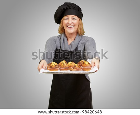portrait of a cook woman showing a homemade muffins tray over a grey background