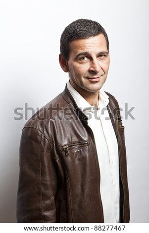portrait of a cool mature man with leather jacket over white background