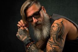 Portrait of a cool, tatooed biker with sunglasses