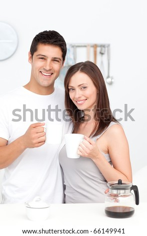 Portrait of a couple drinking coffee during breakfast standing in the kitchen