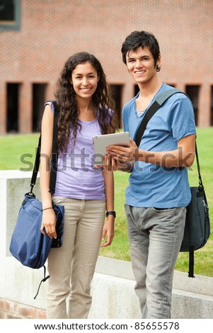 Portrait of a couple holding a tablet computer outside a building