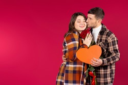 Portrait of a couple inlove on a red background with side space with roses and a big heart in their hands. High quality photo