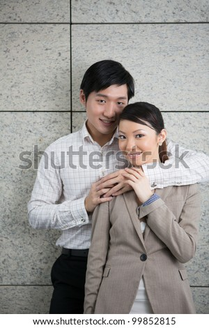 Portrait of a couple leaning against a contemporary wall. - stock photo