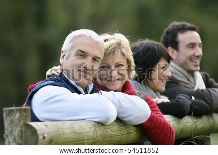 Portrait of a couple leaning against a wooden fence
