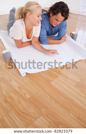 Portrait of a couple looking at their future room on a plan while lying on the floor