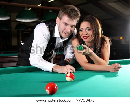 Portrait of a couple playing snooker in a dark club