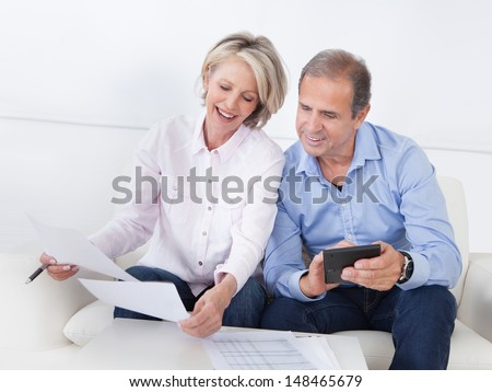 Portrait Of A Couple Sitting On Couch Enjoying Success - stock photo