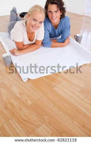 Portrait of a couple with cups of coffee and a plan while lying on the floor