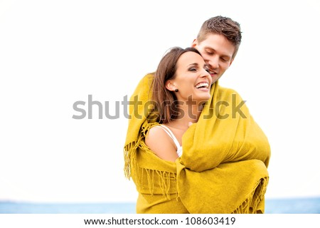 Portrait of a couple wrapped in a blanket while on a sea looking happy