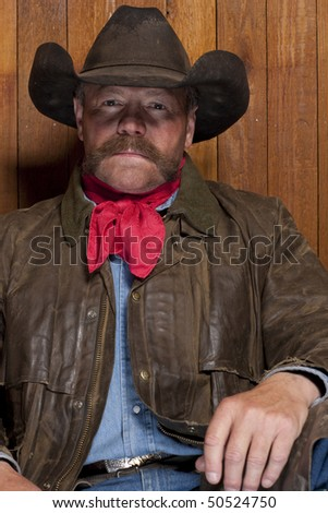 Portrait of a cowboy with a mustache in front of a rough wood wall. He is staring at the camera with a serious expression. Vertical format.