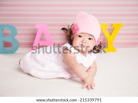 Portrait of a crawling pretty baby with pink hat on the bed in her room. text concept