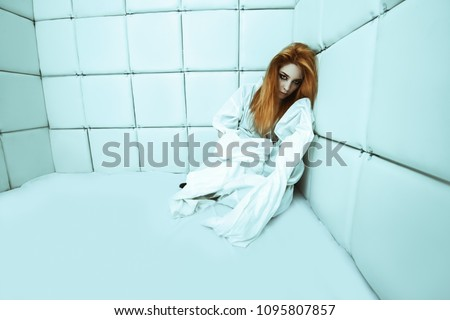 Portrait of a crazy girl dressed in a straitjacket in an isolated room in a madhouse. Stock photo ©