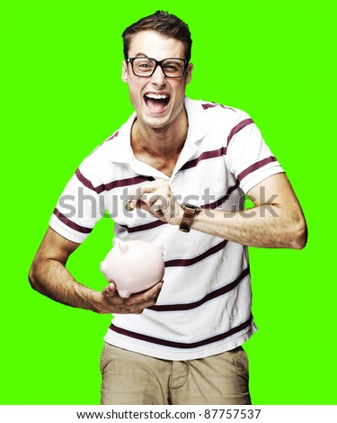 portrait of a crazy young man holding a piggy bank over a removable chroma key background - stock photo