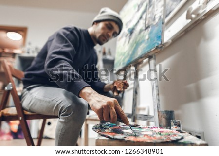 Portrait of a creative man in an art studio at home, creates a picture of oil. Professional artist is painting a picture, mixing oil paint on a palette. Focus on hand with paint and a knife palette