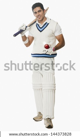 Portrait of a cricket batsman holding a bat and a ball