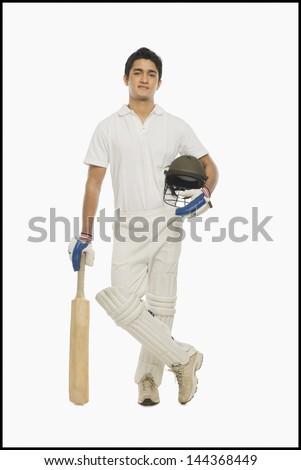 Portrait of a cricket batsman standing with a bat and a helmet
