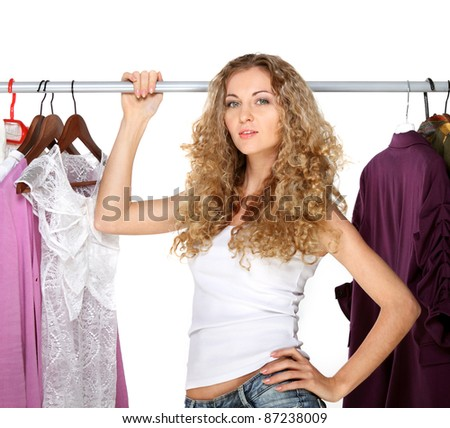 Portrait of a curly blonde beautiful girl selecting clothes