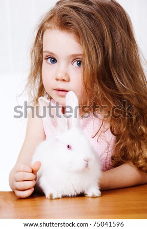 Portrait of a curly girl and white rabbit