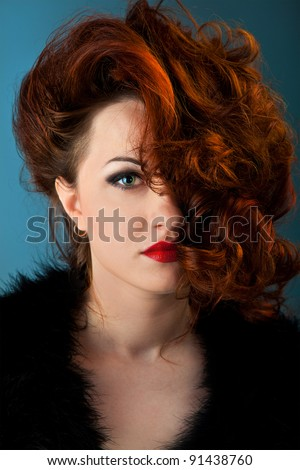 portrait of a curly red- haired girl with red lips wearing a black cardigan