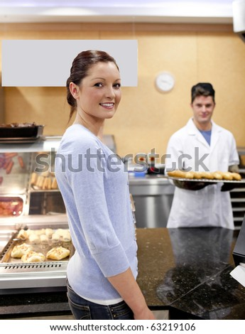 Portrait of a customer in the queue waiting for baguette and bread in a cafeteria with baker in the background - stock photo