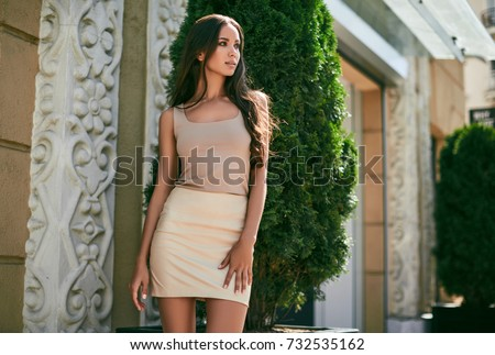 Portrait of a cute and gorgeous latin women in fashion dress posing and smiling along bright european street #732535162