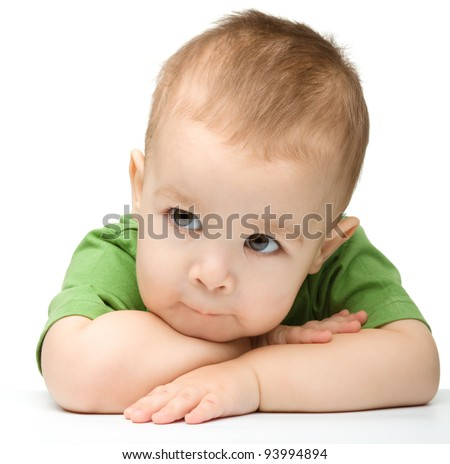 Portrait of a cute and pensive little boy support his head with hands, isolated over white