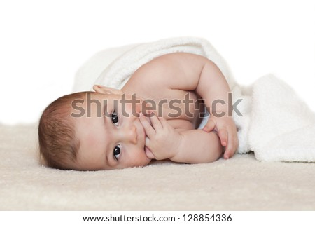 Portrait of a cute baby, boy or girl, in white blanket, sucking his finger.
