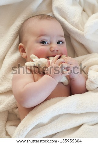 Portrait of a cute  baby, boy or girl, lying on her back, looking up, playing with a soft toy rabbit.