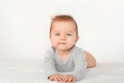 Portrait of a cute baby boy with blue eyes on white background. Healthy childhood innocence concept.