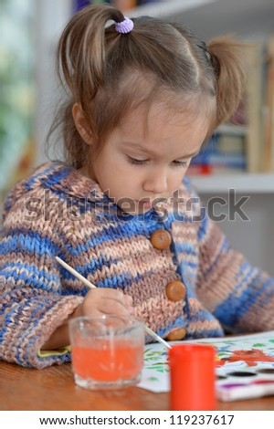 portrait of a cute baby draws in the room
