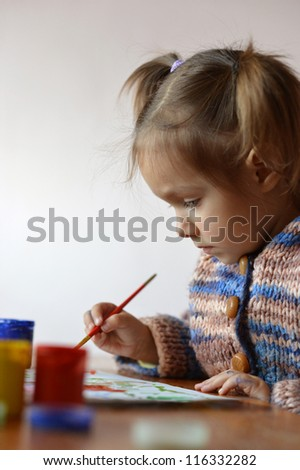 portrait of a cute baby draws paint