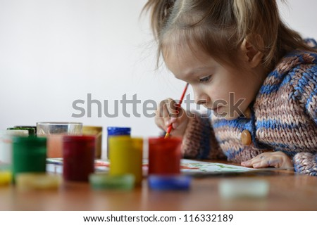 portrait of a cute baby draws paint in the room