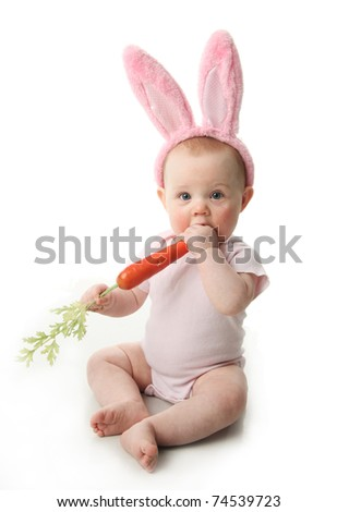 Portrait of a cute baby dressed in Easter bunny ears with a carrot