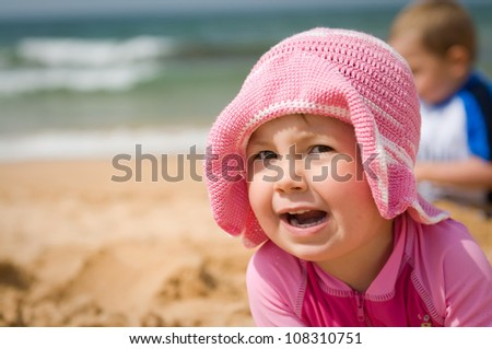 Portrait of a cute baby girl in a hat at the beach