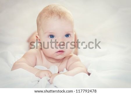 Portrait of a cute baby lies on a blanket