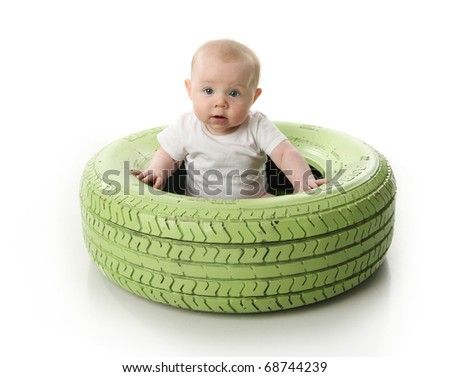 Portrait of a cute baby sitting inside a green painted tire, isolated on white