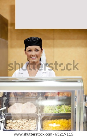 Portrait of a cute baker smiling at a customer in a  cafeteria