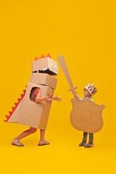 Portrait of a cute boy in costume of knight with cardboard armour is fighting the cardboard dragon. Childhood dreams. Full length portrait on a yellow background.