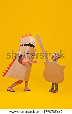 Portrait of a cute boy in costume of knight with cardboard armour is fighting the cardboard dragon. Childhood dreams. Full length portrait on a yellow background. Stock photo ©