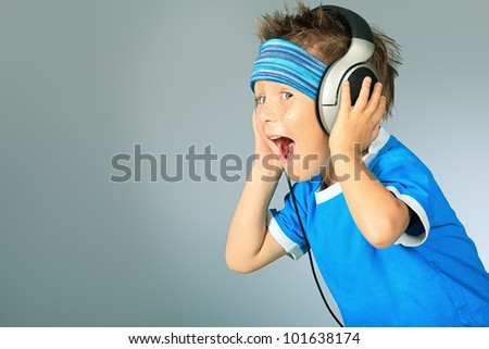 Portrait of a cute boy listening to music on headphones over grey background.