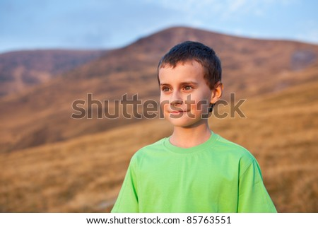 Portrait of a cute boy on Parang mountains, Romania, at sunset