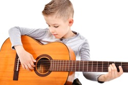 Portrait of a cute boy playing acoustic guitar isolated on white background